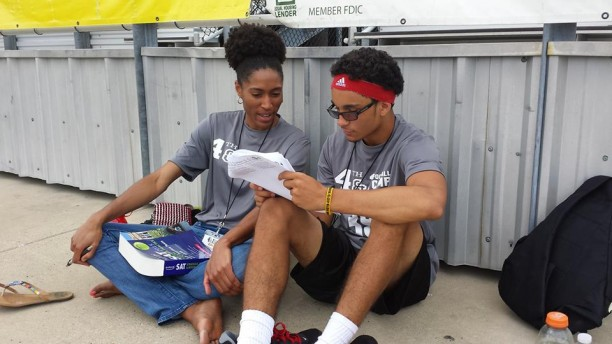 Calling an audible from the sideline, a student-athlete at the 4th and 1 Football Camp decides to study a little SAT Verbal with lead instructor Kim Harbin (l.) during practice on the field of Sam Parker Field in Mt. Pleasant (Photo: Brandi Virden)