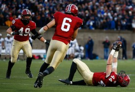Scott Peters (44) holds up the ball after his interception sealed the win for Harvard. (Jared Wickerham/Getty Images)