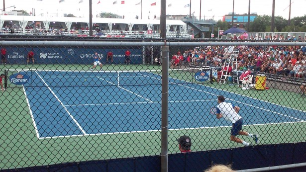 Behind the fence of Court No. 9, Jack Sock (far) hits a forehand winner against No. 14 seed Grigor Dimitrov. Sock came back from match point down in the second set to win the match, 7-5 in the third.