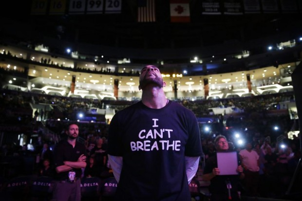 """Los Angeles Lakers' Carlos Boozer stands before team introductions for an NBA basketball game against the Sacramento Kings in Los Angeles. Dozens of athletes in recent weeks have responded to confrontations between authorities and black citizens in Ferguson, Mo., New York and elsewhere by wearing T-shirts bearing such statements as """"I Can't Breathe"""" and """"Hands Up, Don't Shoot!"""" (AP Photo/Jae C. Hong, File)"""